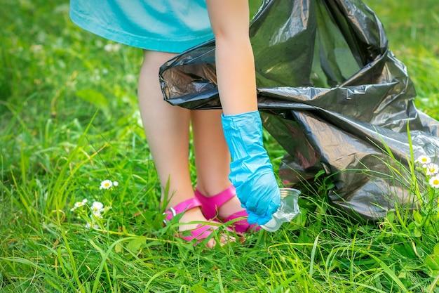 De hand van het kind reinigt park van plastic gebruiksvoorwerpen in het gras in het park