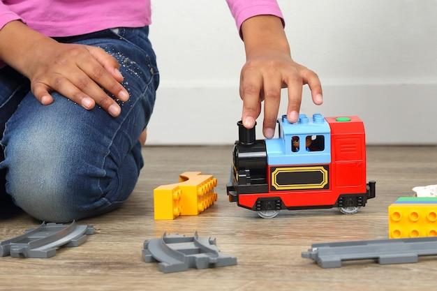 De hand van het kind spelen met de kinderbaan