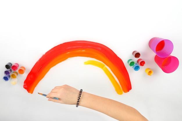 De hand van het kind tekent een regenboog op een wit papier