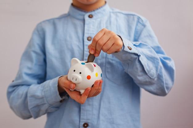 De hand van het kind zet in witte piggybank geldmunten.