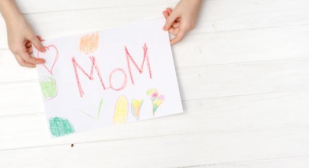 De hand van het kleine kind met geschilderde prentbriefkaar