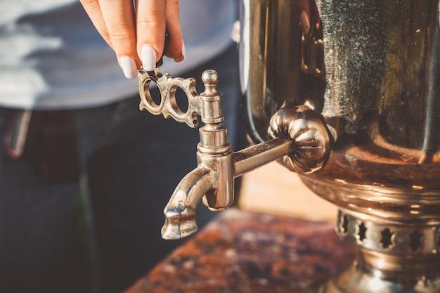 De hand van het meisje draait de kraan van de oude samovar, close-up