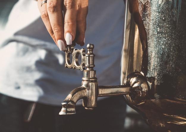 De hand van het meisje draait de kraan van de oude samovar