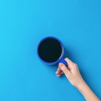 De hand van het meisje houdt een blauw glas met zwarte koffie op een helderblauwe achtergrond. een vrouwenhand met een populaire verkwikkende drank.