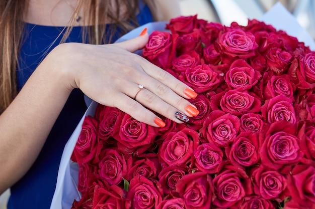 De hand van het meisje met een diamanten ring over een boeket van rode bloemen.