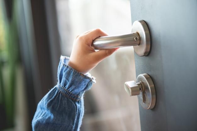 De hand van het meisje opent de deur