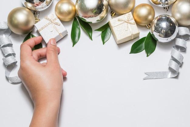 De hand van het meisje pakt de geschenkdoos op. kerstmisfestival, achtergrond met exemplaar spac