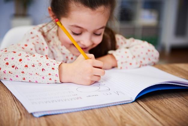 De hand van het meisje schrijft in haar notitieboekje