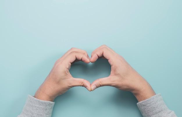 De hand van het zakenmangebruik maakt hartvorm op blauwe achtergrond. het is valentijnsdag en gezondheidscontrole-concept.