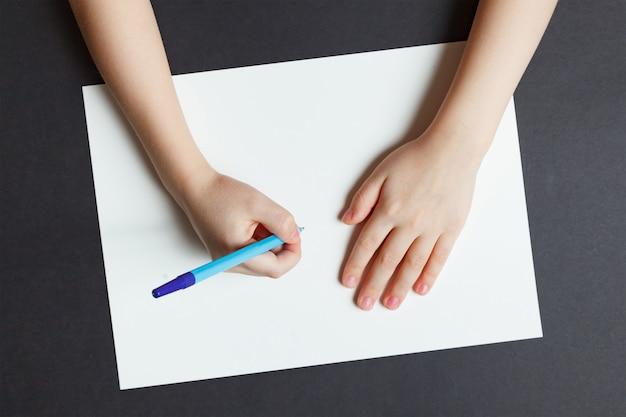 De hand van kinderen met een pen op een witboek