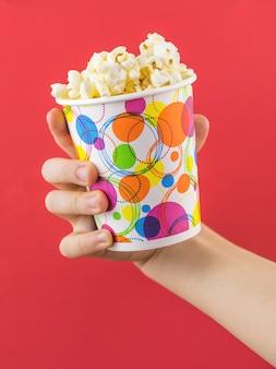 De hand van kinderen met kleurrijke glazen popcorn op een rode muur
