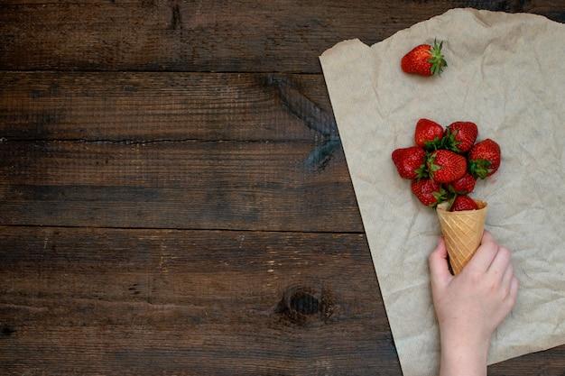 De hand van kinderen neemt aardbeien