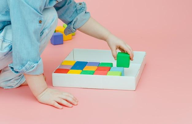 De hand van kinderen neemt houten gekleurde kubussen uit een witte doos.