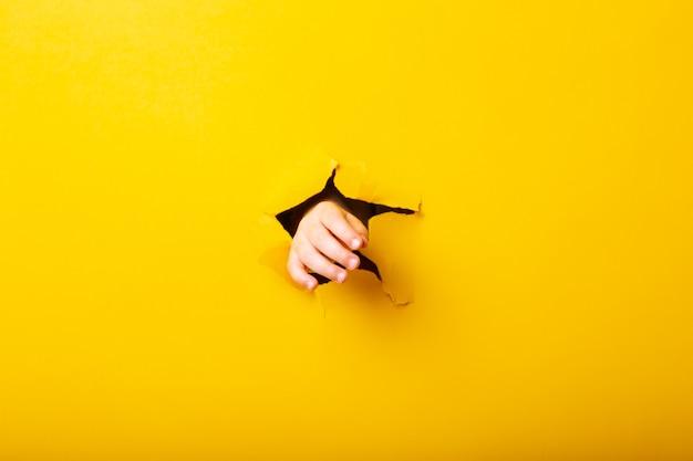 De hand van kinderen reikt door het gat in het gescheurde papier op een gele achtergrond.