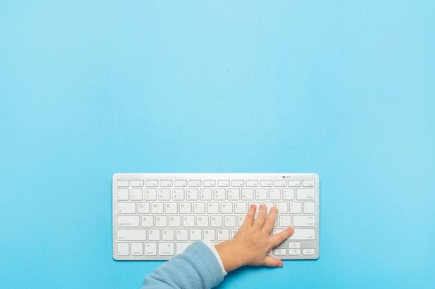 De hand van kinderen rust op het toetsenbord. bovenaanzicht, platliggend