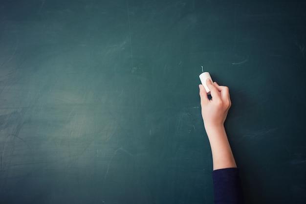 De hand van kinderen schrijft met krijt