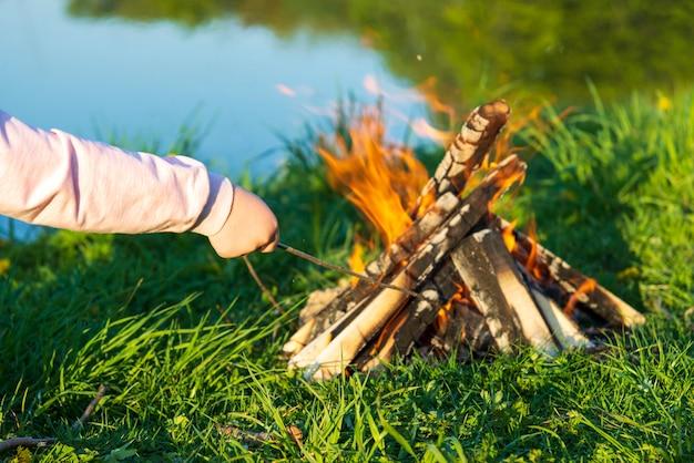 De hand van kinderen steekt een houten tak in een brandend vuur bij de rivier in de zomer