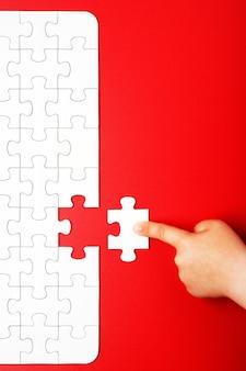 De hand van kinderen verplaatst een stuk van witte puzzel op een rode achtergrond