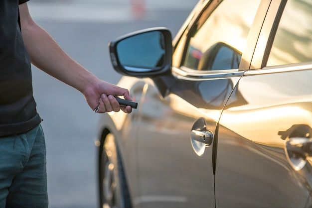 De hand van mannen drukt op de auto-alarmsystemen van de afstandsbediening