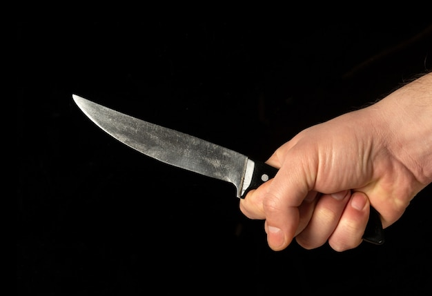 De hand van mannen houdt een scherp mes