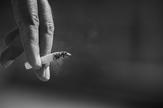 De hand van mannen pakt sigaretten op.