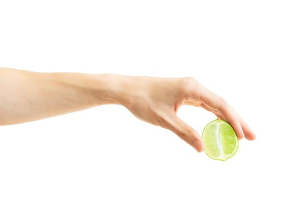 De hand van mensen zet een plak van kalk neer die op wit wordt geïsoleerd