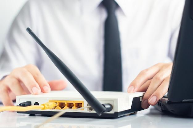 De hand van netwerkingenieur die modem controleren heeft naast laptop op lijst, netwerkcommunicatie