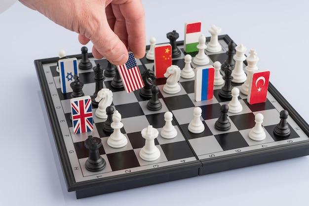 De hand van politici beweegt een schaakstuk met een vlag conceptuele foto van een politiek spel