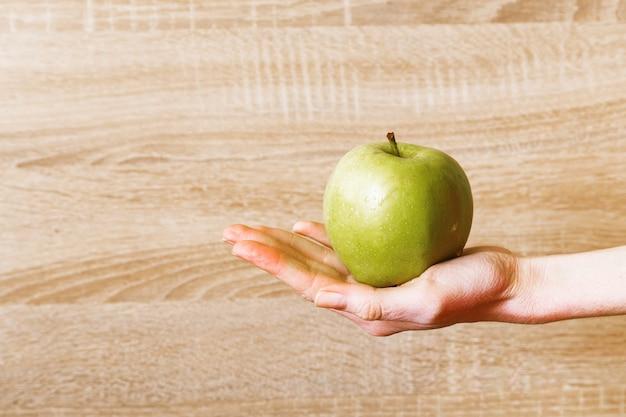 De hand van vrouwen houdt groene appel.