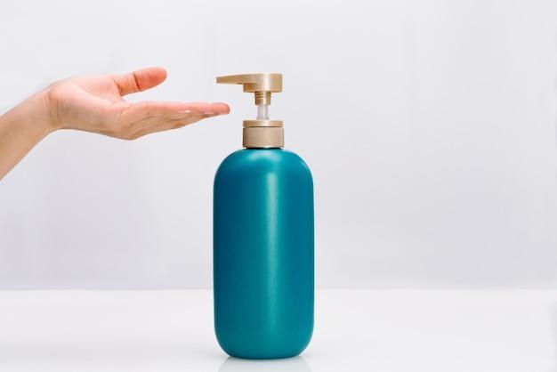 De hand van vrouwen past de veredelingsmiddelfles van het haarshampoo op witte achtergrond toe.