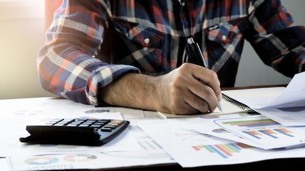 De hand van zakenlieden wordt geschreven rekenings financiële rapportage