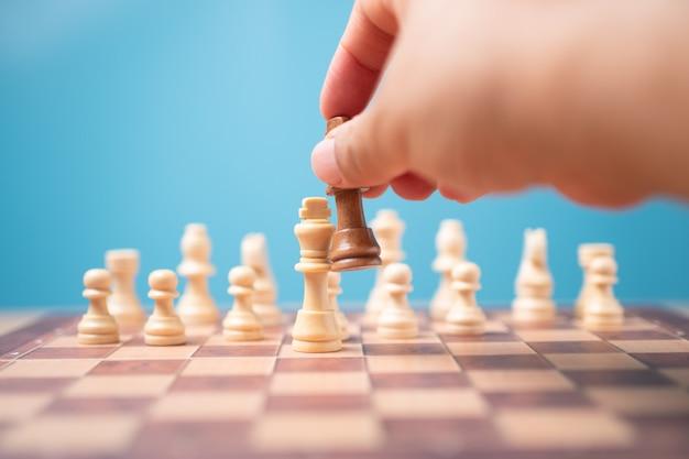 De hand van zakenman die bruin koningsschaak en schaakmatconcurrent houdt en wint de spelen.