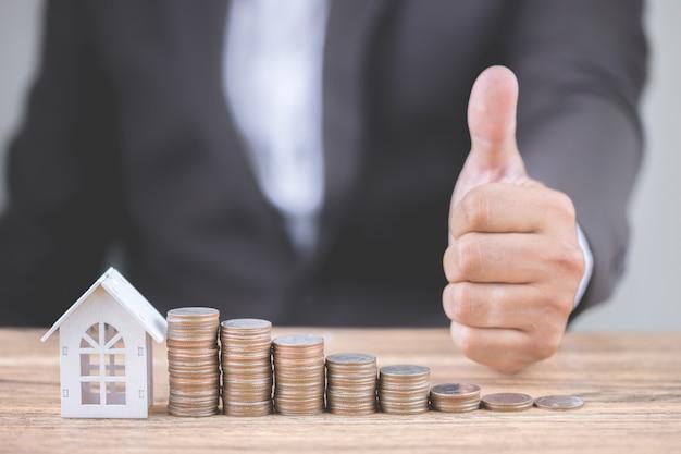 De hand van zakenman toont duimen met geld van muntstapelstap het groeien omhoog
