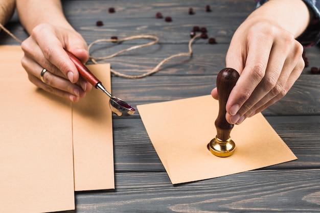 De hand verzegelende envelop van de vrouw met zegel
