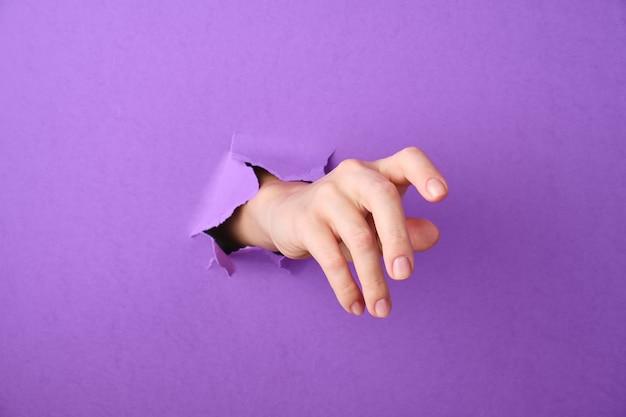 De hand wordt door een gat in de papieren achtergrond gestoken