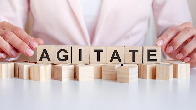 De hand zet een houten kubus met de letter agitate. het woord is geschreven op houten kubussen die op het witte oppervlak van de tafel op de roze achtergrond staan.