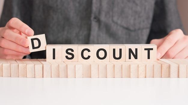De hand zet een houten kubus met de letter d van het woord discount.