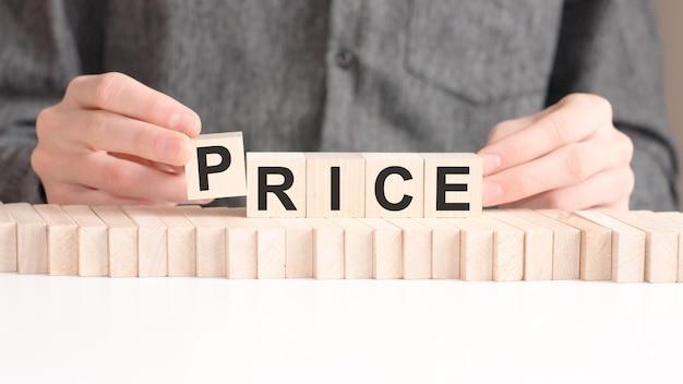 De hand zet een houten kubus met de letter p van het woord price. het woord is geschreven op houten kubussen die op het witte oppervlak van de tafel staan.