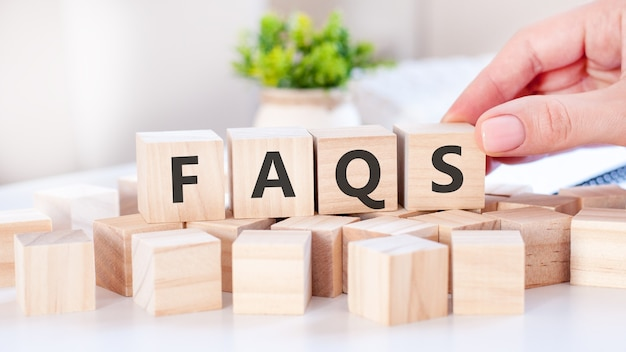 De hand zet een houten kubus met de letter s van het woord faqs. het woord is geschreven op houten kubussen die op het witte oppervlak van de tafel staan. communicatie- en bedrijfsconcepten