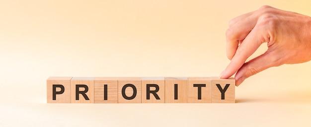 De hand zet een houten kubus met de letter y van het woord priority. het woord is geschreven op houten kubussen die op het gele oppervlak van de tafel staan.