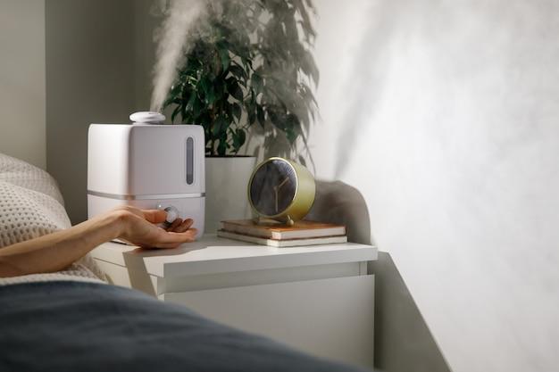 De hand zet luchtbevochtiger op nachtkastje thuis aan