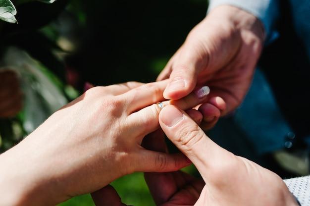 De handbruidegom draagt gouden ring, op de vingerhand van de bruid. huwelijksceremonie.