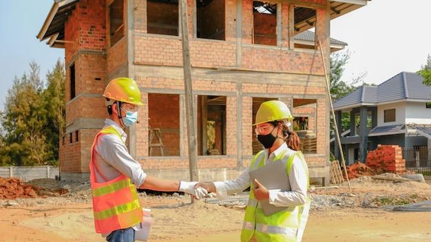 De handdruk van het ingenieursteam na het ontmoeten van het werkplanindustrieproject op de bouwplaats