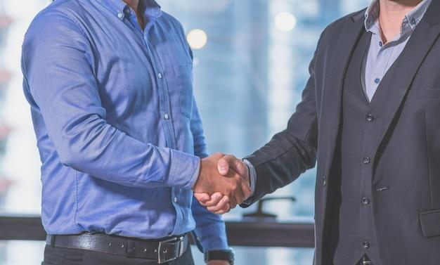 De handdruk van het twee zakenmanpartnerschap komt zaken samen in het het werkbureau overeen