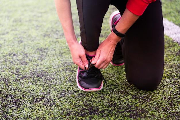 De handen binden schoenveter op sportschoenen bij het sportenstadion