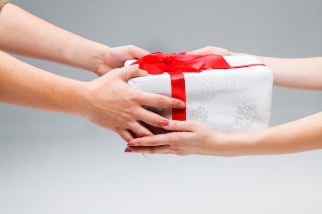 De handen die een cadeau geven en ontvangen op een witte achtergrond