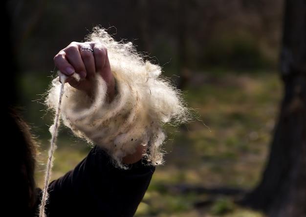 De handen die met de hand wollen fleece spinnen