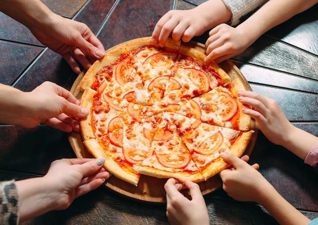 De handen die pizzaplakken van houten lijst nemen, sluiten omhoog mening.
