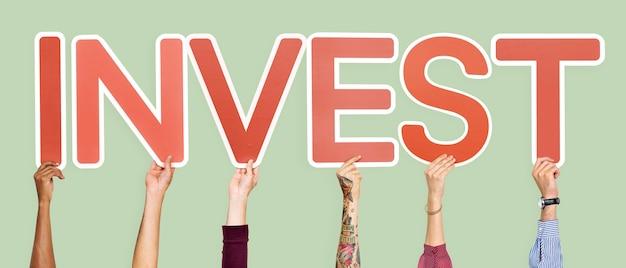 De handen die rode brieven steunen die het woord vormen investeren