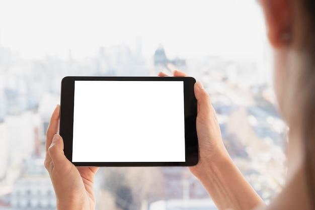 De handen die tablet houden met defocused achtergrond